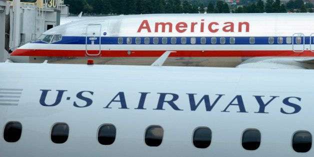 FILE - This Tuesday, Aug. 13, 2013 file photo shows an American Airlines plane and a US Airways plane at parked at Washington