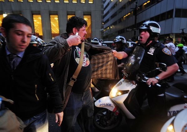 Members of Occupy Wall clash with police during a celebration march after learning that they can stay on Zuccotti Park in New