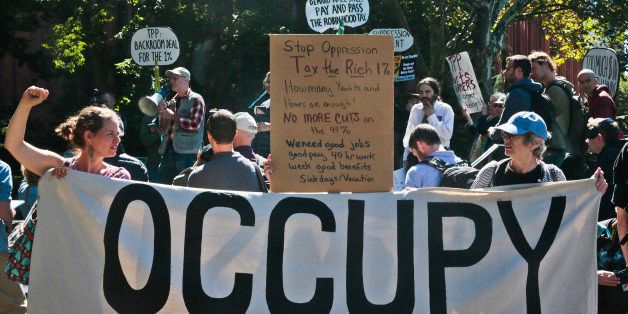 Protesters representing the Occupy Wall Street  movement, rally on Tuesday, Sept. 17, 2013, in Washington Square Park in New