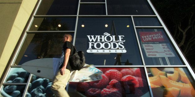 In this Oct. 31, 2011 photo, a man carries a surfboard past a Whole Foods store in Santa Monica, Calif. Whole Foods Market In