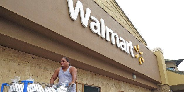 A man pushes a shopping cart outside of a Walmart store that boarded its entrance and closed early in Kailua-Kona, Hawaii, Th
