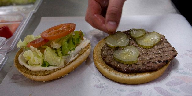 An employee places a pickle in a whopper burger at a Burger King restaurant in Basildon, U.K., on Wednesday, Sept. 8, 2010. B
