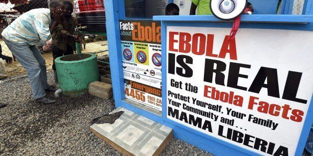 Liberians wash their hands next to an Ebola information and sanitation station raising awareness about the virus in Monrovia