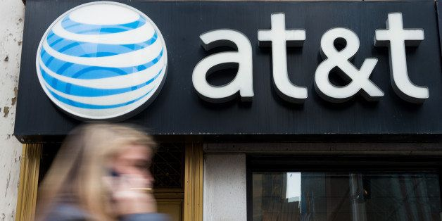 A pedestrian talks on a cell phone while walking past an AT&T Inc. store in New York, U.S., on Monday, Jan. 27, 2014. AT&T In