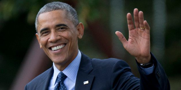 President Barack Obama waves as he walks across the South Lawn of the White House in Washington, Tuesday, Oct. 7, 2014, to bo