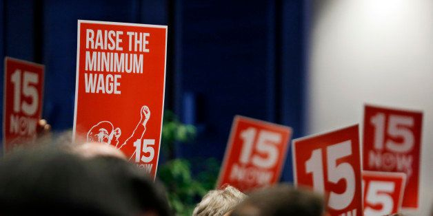 Signs supporting a $15 minimum wage are held up at an inaugural event for new Seattle City Council members, city attorney and