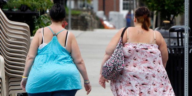 In this  June 17, 2013  photo, two women cross the street in Barre, Vt. In its biggest policy change on weight and health to