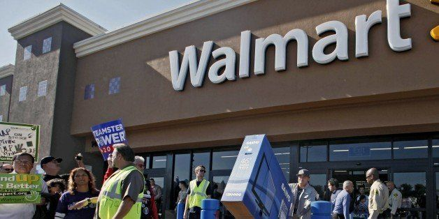 Shopper Jose Alvarez, right, carries out a newly-purchased television past protestors outside a Walmart store Friday Nov. 23,