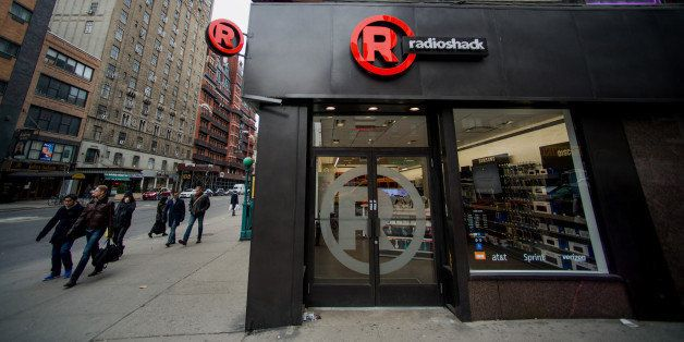 Pedestrians pass in front of a RadioShack Corp. store in New York, U.S., on Sunday, March 2, 2014. RadioShack Corp. is schedu