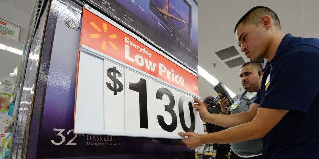 An employee lowers the price on televisions at the Walmart in the Crenshaw district of Los Angeles on Black Friday, November