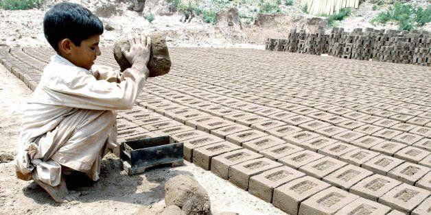 ISLAMABAD, PAKISTAN:  Pakistani boy Salim, 7, makes bricks at a brick factory in Islamabad, 12 June 2004.  According to the I