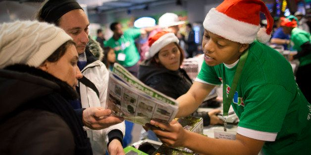 An employee explains sale prices to customers at the Times Square Toys R' Us, Thursday, Nov. 28, 2013, in New York. Instead o