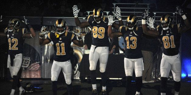 ADDS SIGNIFICANCE OF THE RAISED ARMS -- Members of the St. Louis Rams raise their arms in awareness of the events in Ferguson