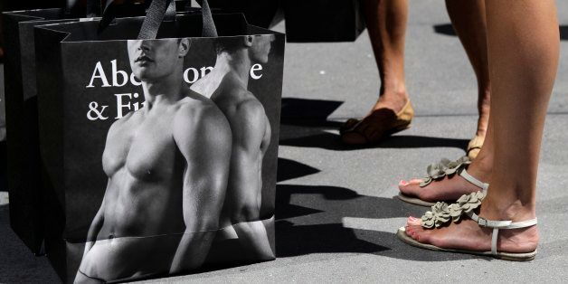 In this Tuesday, July 10, 2012, photo, young women pause with their Abercrombie & Fitch shopping bags on the sidewalk alo