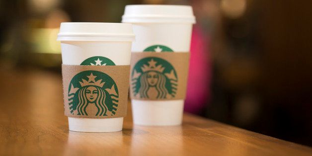 The Starbucks Corp. logo sits on carboard coffee cups inside a Starbucks coffee shop in London, U.K., on Monday, June 9, 2014