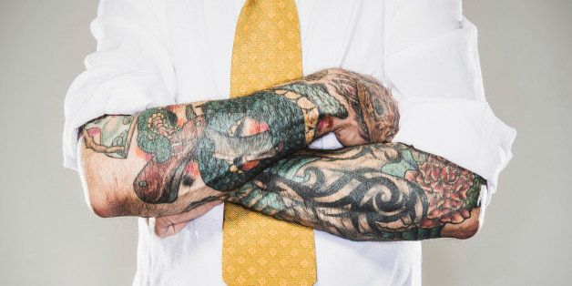 A business man stands with his tattooed arms folded across his white collared shirt and tie. Two forearm sleeve tattoos. Representing a new generation of modern business standards and style.