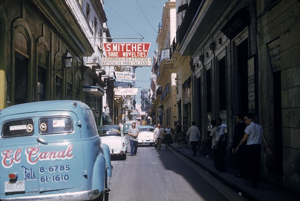 1950 - Cars are parked along a narrow street as pedestrians walk in the shade in Havana, Cuba. At the time, the cars were con