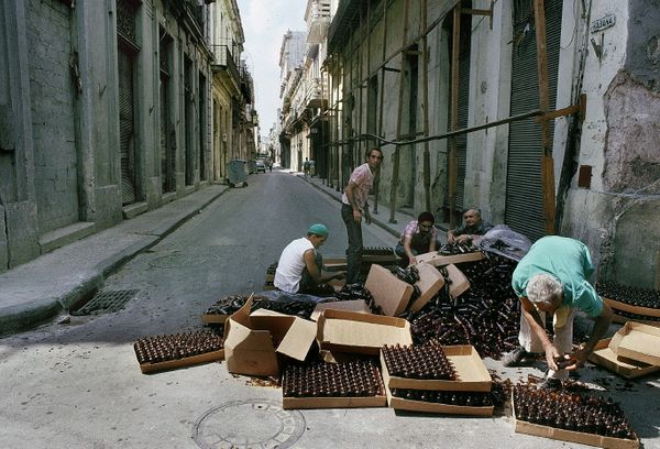 1988 - Men sort empty bottles on a street in Havana.