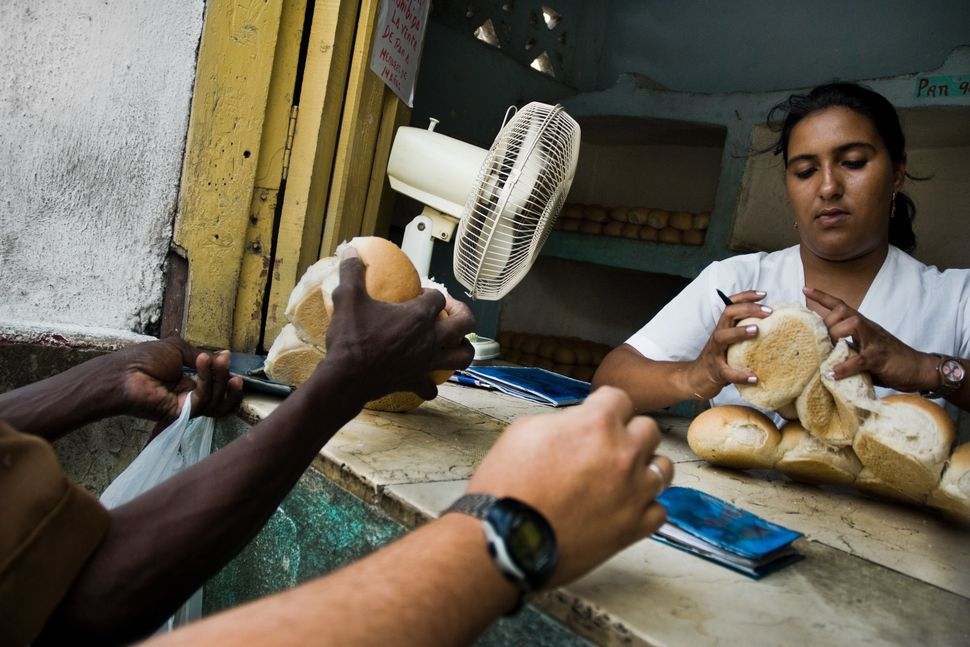 2008 - A young Cuban woman distributes a limited amount of bread to her fellow citizens according to quotas of the Cuban rati