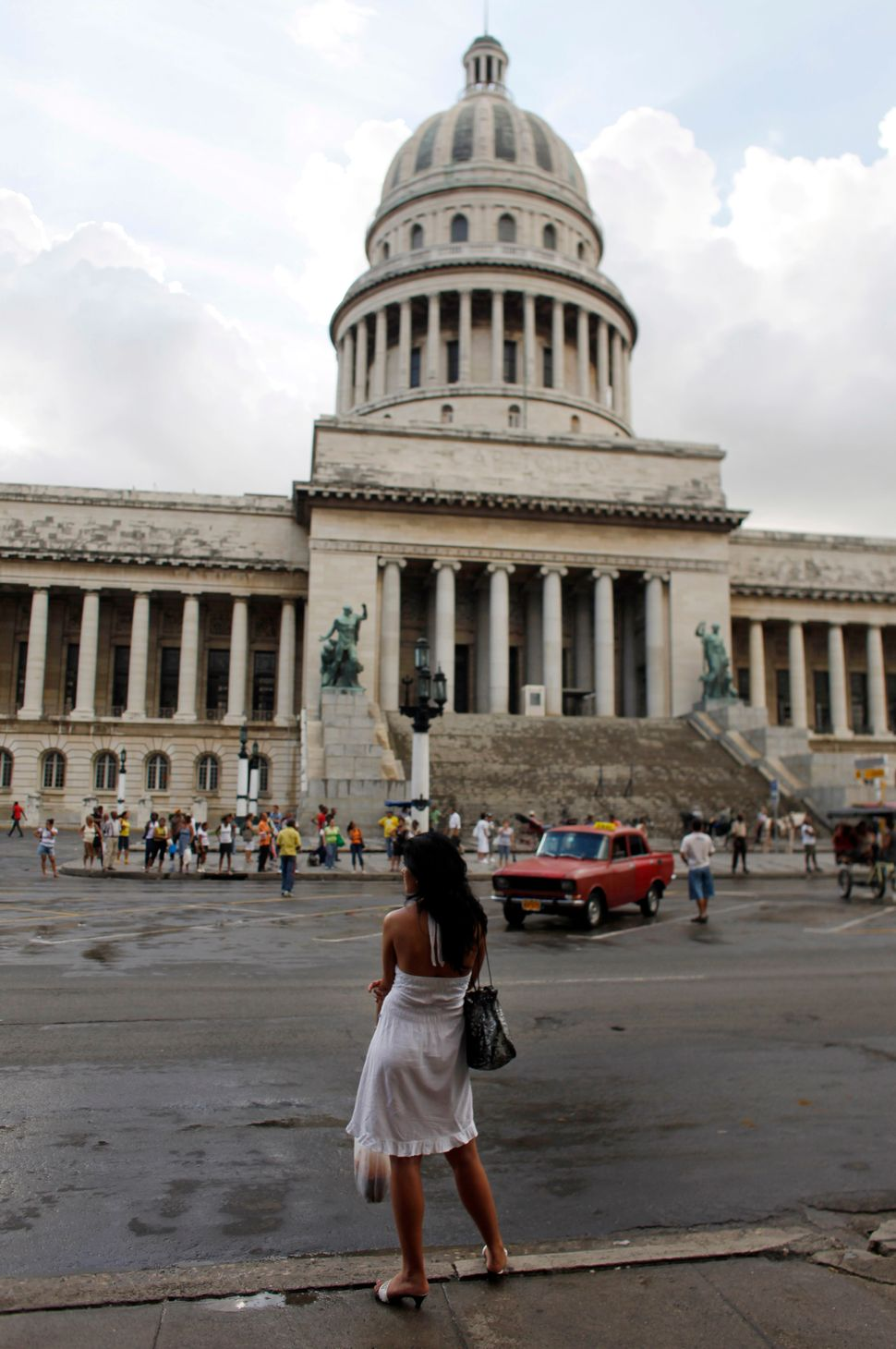 2010 - A woman waits for a bus in front of the Capitol building in Havana.