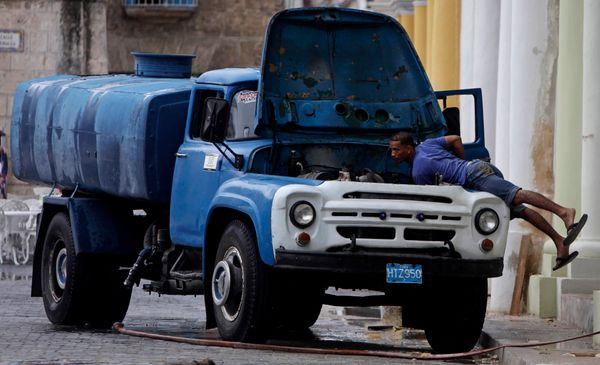 2011 - A man checks the engine of his water cistern truck in Old Havana.