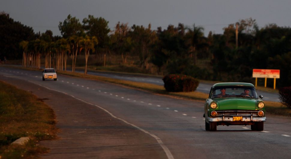 2011 - Two men drive down the highway in a classic car in Soroa.