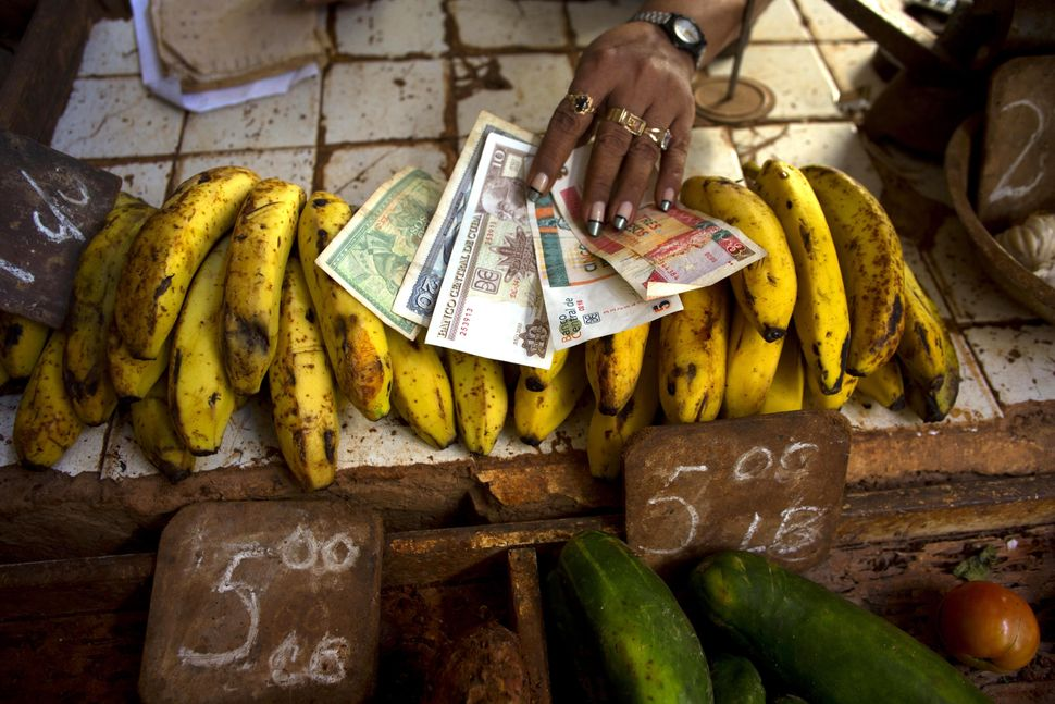 2013 - A food vendor spreads out bananas. Cuba is the only country in the world that mints two national currencies, a bizarre