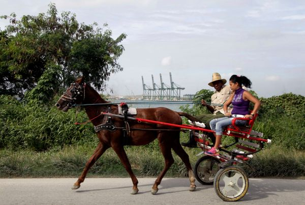 2013 - A man drives a horse drawn carriage past a port under construction in Mariel Bay.