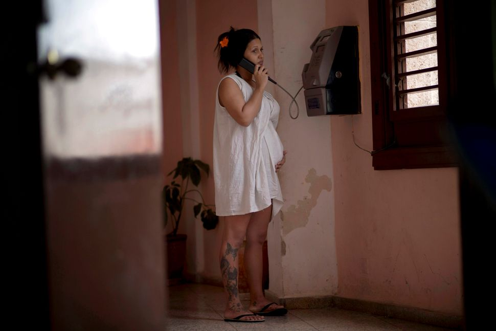 2014 - A pregnant woman holds her belly while she talks on a public phone at a special maternity unit for high-risk pregnanci