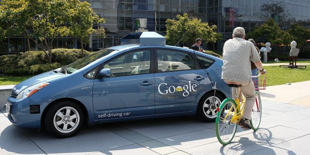 MOUNTAIN VIEW, CA - SEPTEMBER 25:  A bicyclist rides by a Google self-driving car at the Google headquarters on September 25,