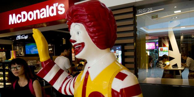 FILE - In this Thursday, July 31, 2014 file photo, a customer walks past a statue of Ronald McDonald on display outside a McD