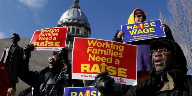 In this Thursday, Nov. 20, 2014 photo, supporters of legislation that will raise the minimum wage in Illinois rally outside t