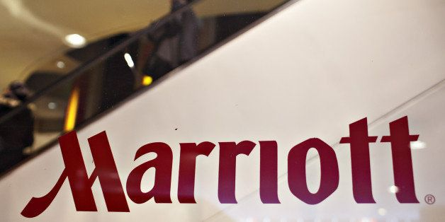 UNITED STATES - FEBRUARY 11:  Guests ride an escalator in the background of a Marriott logo on a window outside a Marriott ho