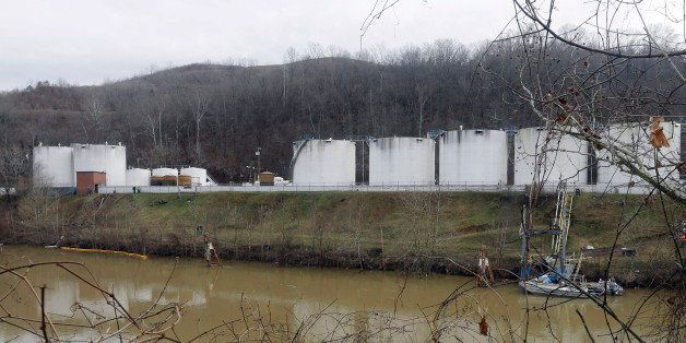 In this Jan. 13, 2014, photo, workers, left, inspect an area outside a retaining wall around storage tanks where a chemical l