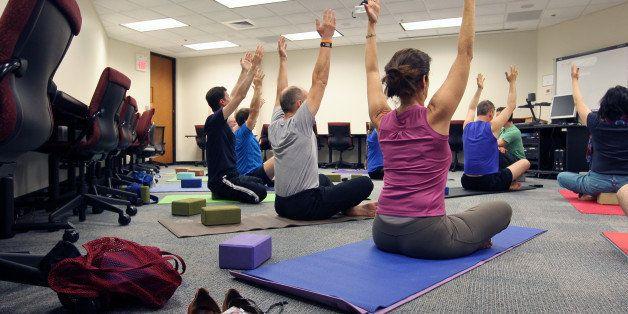 CAMBRIDGE, MA - JUNE 3: Noon office yoga class at Draper Laboratory, one of Draper's employee wellness initiatives. Draper is