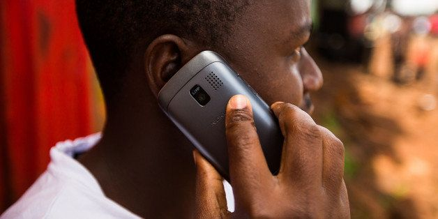 A resident speaks on a Nokia Asha mobile phone on a street in Nairobi, Kenya, on Sunday, April 14, 2013. In the six years sin