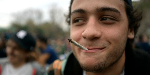A young man smokes a marijuana cigarette at a park where people gathered to mark the First Worldwide...