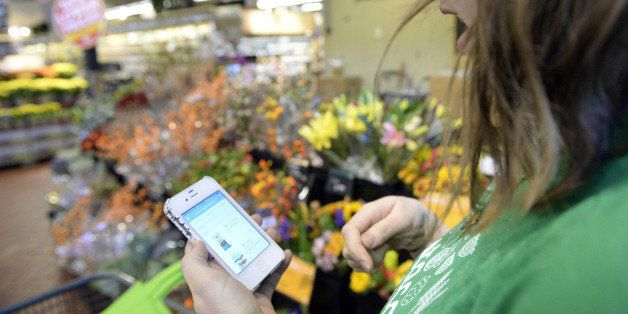 DENVER, CO. OCTOBER 28: Kaitlin Myers a shopper for Instacart studies her smart phone as she shops for...
