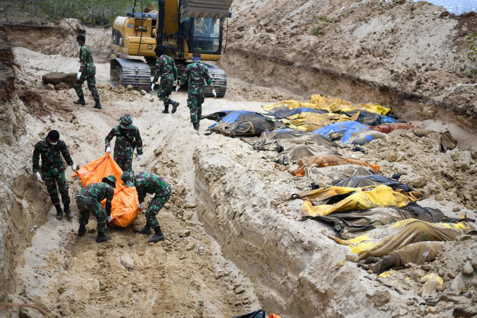 Indonesian soldiers buried quake victims in a mass grave in Poboya on Tuesday.