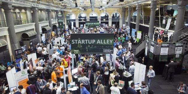 Exhibitors promote their business start-up companies in the main hall titled 'Startup Alley' at the Disrupt Europe 2014 confe