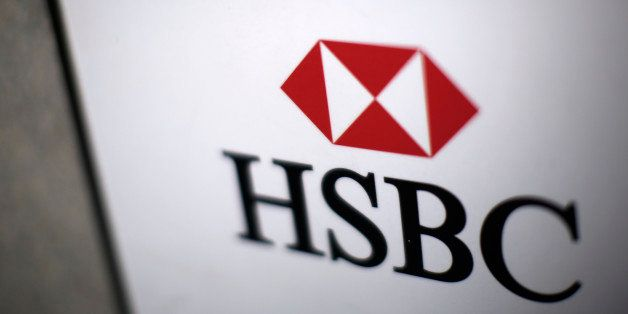 A logo sits on a sign outside a HSBC Holdings Plc bank branch in London, U.K., on Monday, Dec. 9, 2013. HSBC may sell a stake