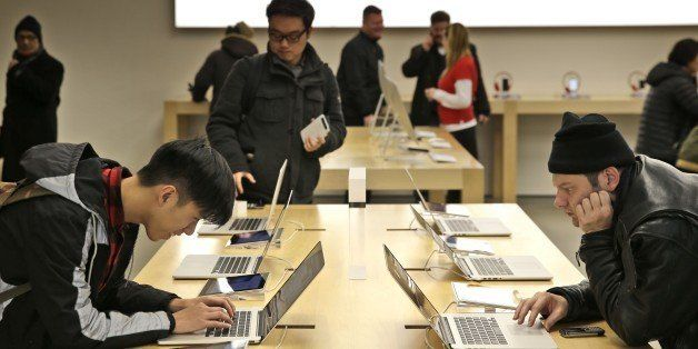Customers looks over the products at an Apple store in New York, Thursday, Jan. 8, 2015. (AP Photo/Seth Wenig)