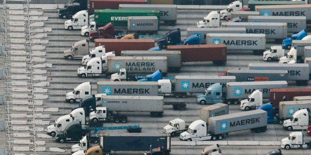 Trucks transporting A.P. Moeller-Maersk A/S branded containers wait in line with other trucks in this aerial photograph taken