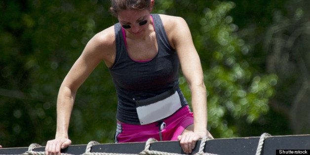 Young woman participant of charity obstacle course climbs up and over the net barrier.