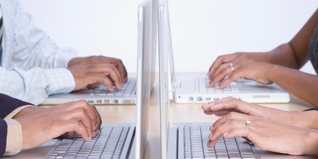 Four business people working on laptop computers, close-up on hands