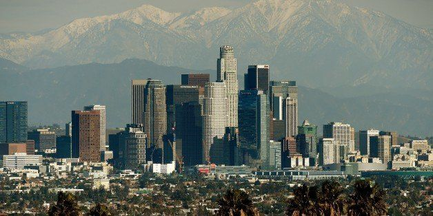 The Los Angeles city skyline stands in front of the snow covered San Gabriel Mountains after a snowstorm hit the region on De