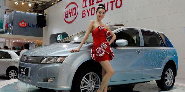 A model poses next to a new BYD e6 electric vehicle of Chinese automaker BYD Auto at the Shanghai International Auto Show on