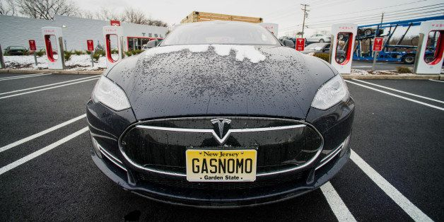 A Model S electric vehicle (EV) with a personalized license plate charges at a supercharger station at the Tesla Motors Inc.