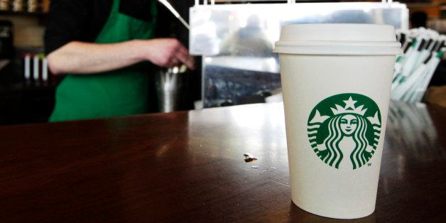 A Starbucks drink waits for a customer to pick it up as barista Josh Barrow prepares another at left, Friday, April 27, 2012,