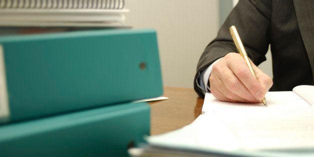 Busy businessman writing paperwork